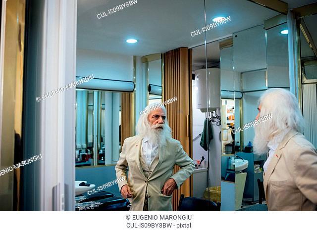 Senior businessman looking into mirror in salon