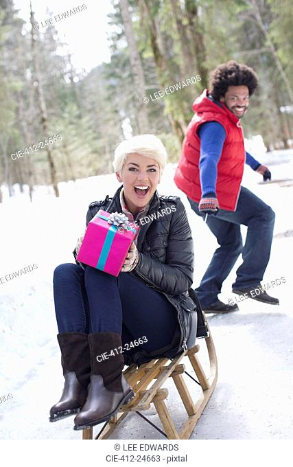 Man pulling woman with gift on sled in snow