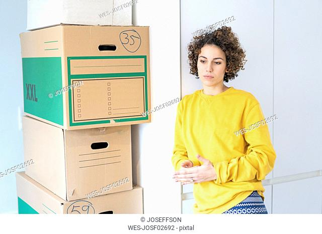 Serious woman at home with cardboard boxes