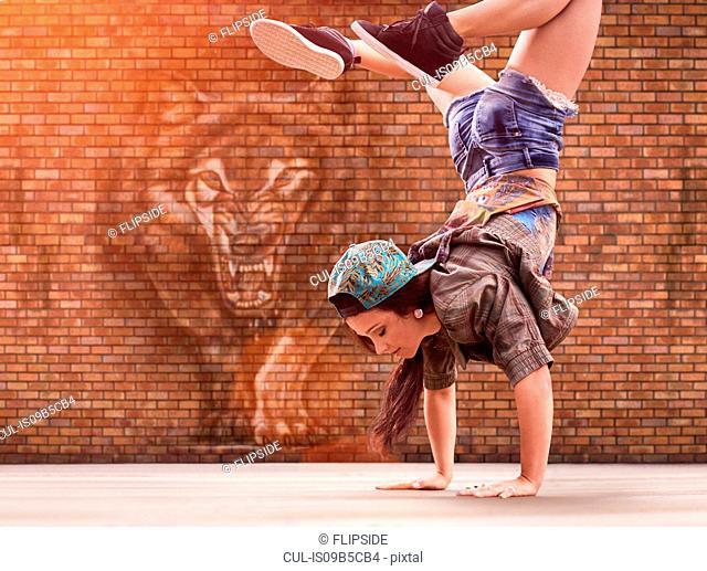 Dancer doing back flip, tiger street art in background