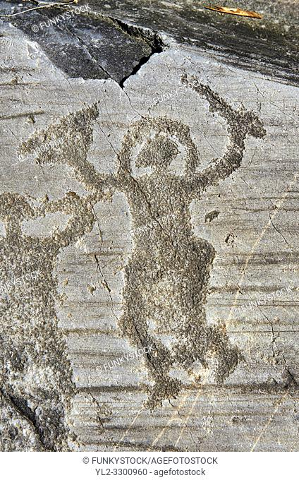 Petroglyph, rock carving, of a warrior wearing a helmet and carrying a sword and shield. Carved by the ancient Camuni people in the iron age between 1000-1600...