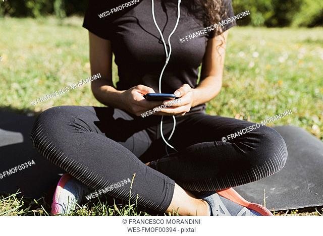 Sporty young woman having a break on a meadow using cell phone