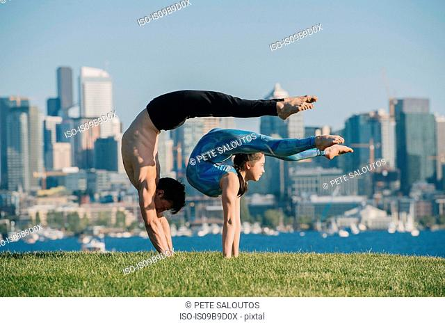 Teenage girl and young man, outdoors, balancing on hands in yoga position