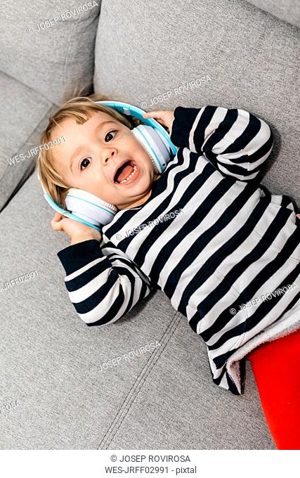 Portrait of toddler girl lying on the couch listening music with headphones