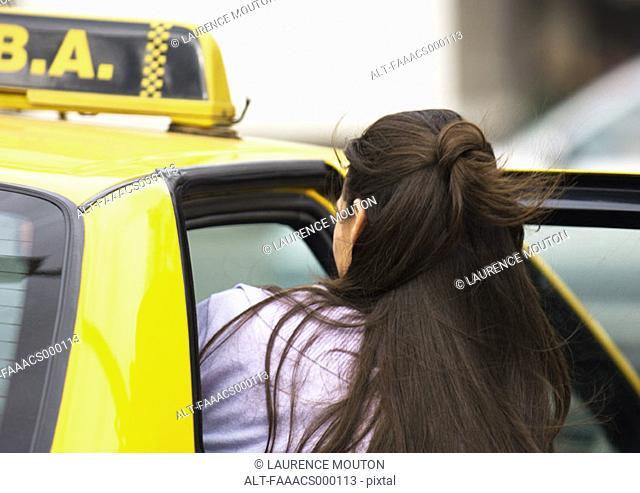Woman getting in taxi