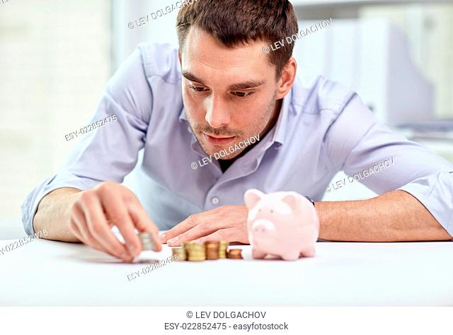 business, people, finances and money saving concept - businessman with piggy bank and coins at office