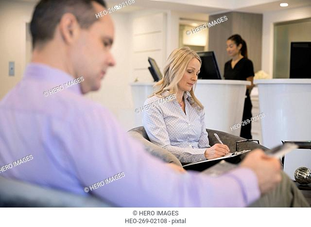 Patient filling out paperwork in clinic waiting area