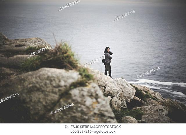 Lonely girl in lighthouse Cape Finisterre. La Coruña province, Galicia, Spain