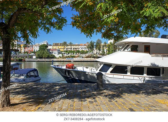 Tour boats moored along the Guadalquivir river with views of houses and apartments in the Triana barrio quarter of Seville - Sevilla - Andalucia, Spain