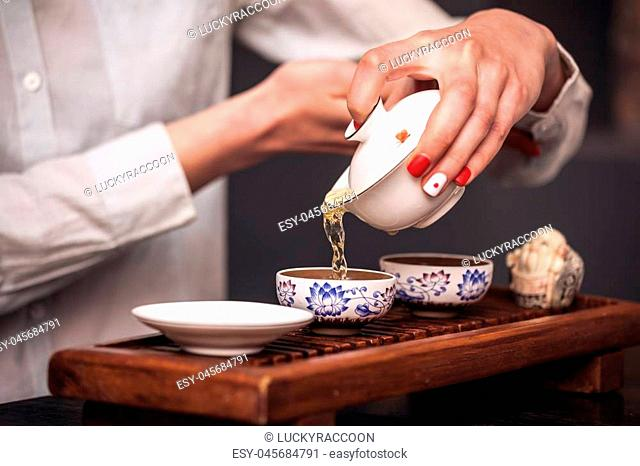 Cropped shot of woman pouring teacup in traditional chinese teaware