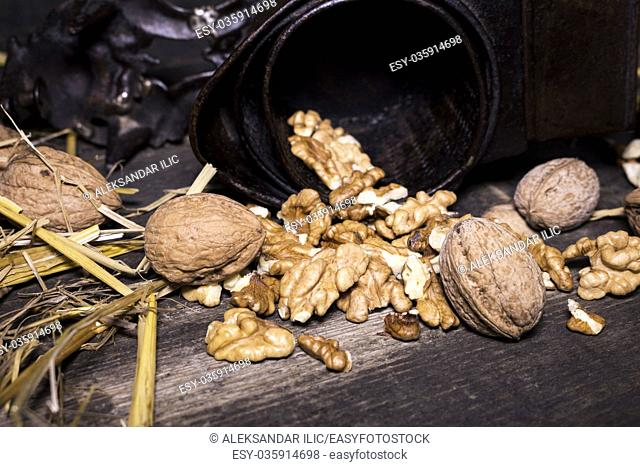 Wallnuts and hand walnuts grinderon a wooden surface