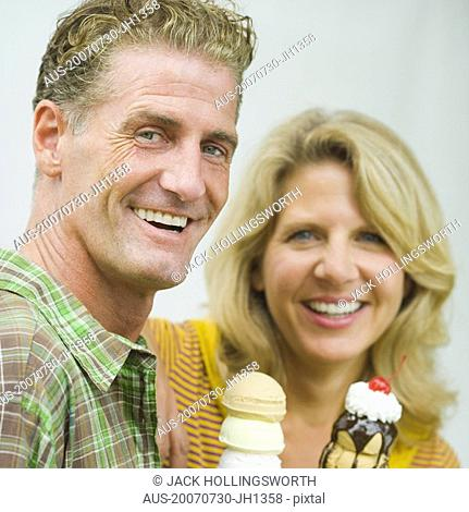Portrait of a mature couple holding ice cream cones and smiling