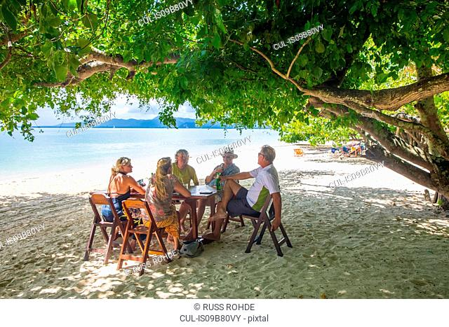 Friends relaxing at dining table on beach, Koh Rang Yai, Thailand, Asia