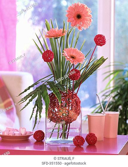 Arrangement of gerberas, dwarf palm, holly fern, wicker balls