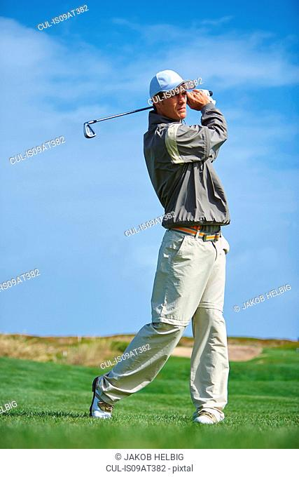 Full length front view of golfer holding golf club taking golf swing