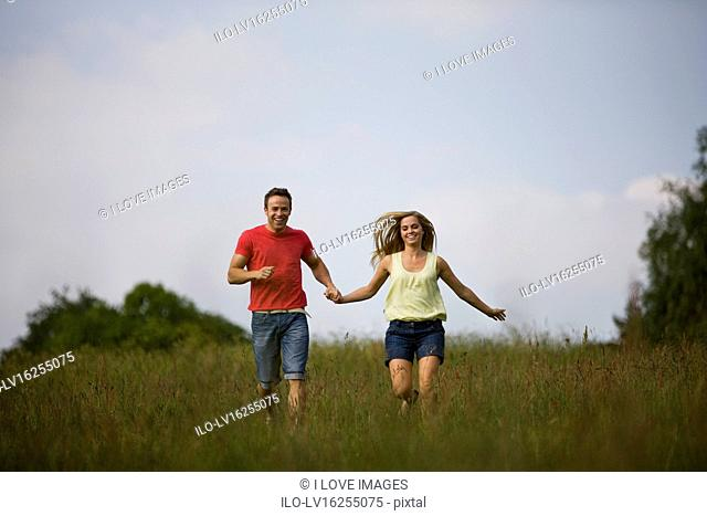 A young couple running through a field hand in hand