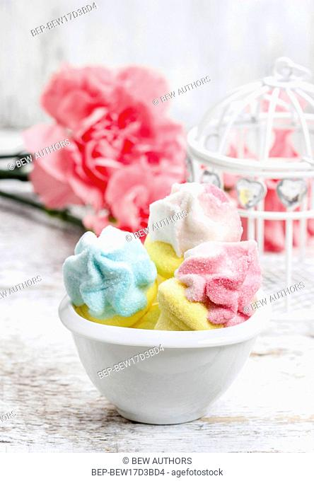 Marshmallows in white bowl among pink carnations