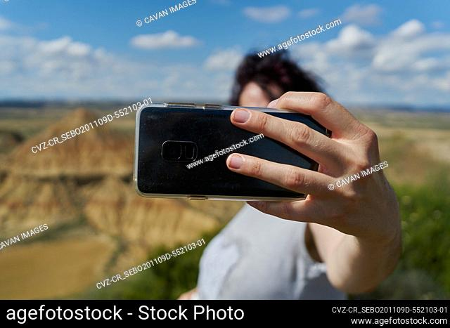 A woman makes a selfie with her mobile phone in the Bardenas Reales desert in Spain