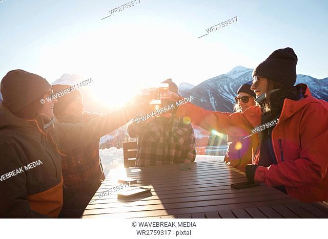 Skiers friends toasting glasses of beer in ski resort