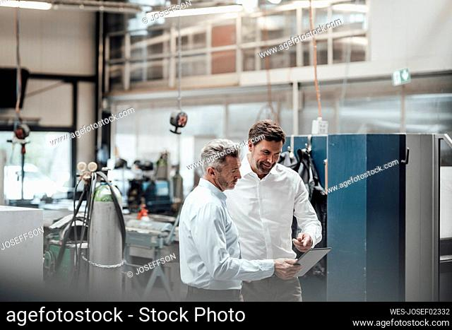 Businessman discussing with male colleague over digital tablet in industry