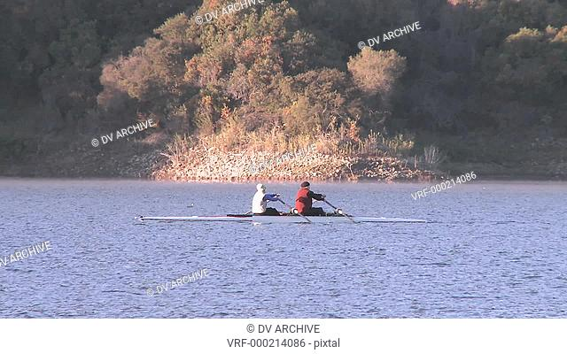 Panning two people rowing a double scull on Lake Casitas in Oak View, California