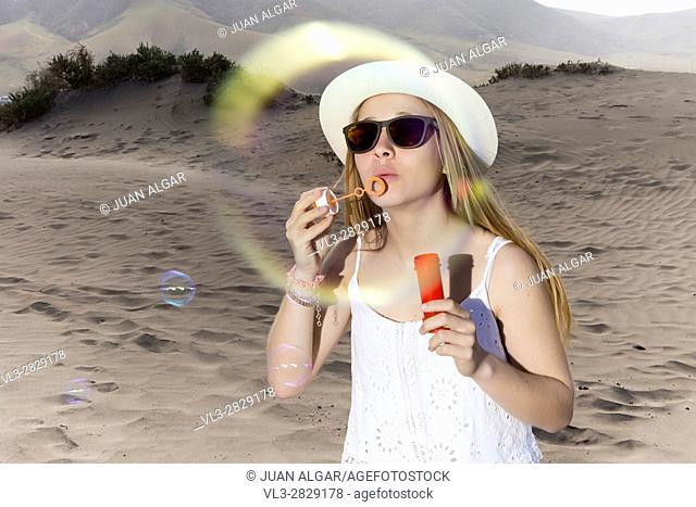 Woman blowing the bubbles at camera. Horizontal outdoors shot
