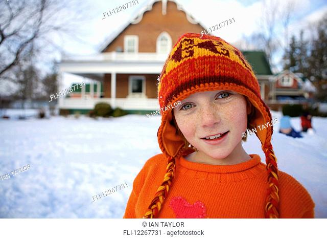 Portrait of girl in an orange wool hat in winter; Picton, Ontario, Canada