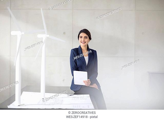 Portrait of smiling young woman with blueprint, wind turbine models and tablet in office