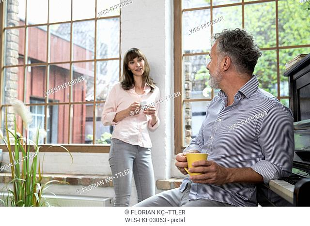 Mature couple at home taking a break, talking and drinking coffee