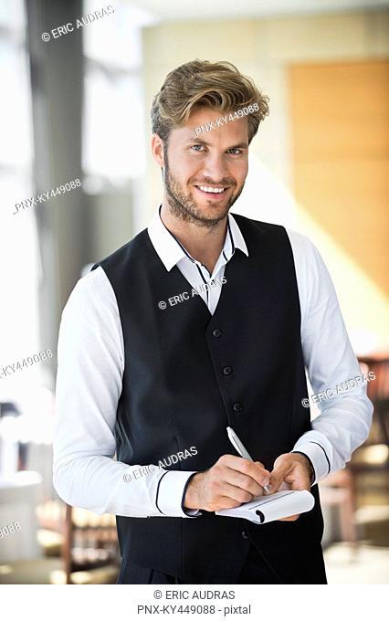 Portrait of a waiter taking order in a restaurant