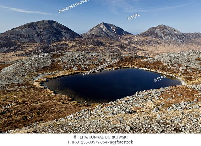 View of small freshwater lochan at top of 'marilyn' hill, with Paps of Jura mountain peaks in background, Glas Bheinn, Isle of Jura, Inner Hebrides, Scotland