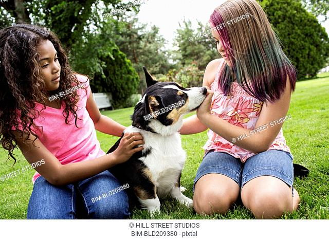 Girls petting dog in backyard