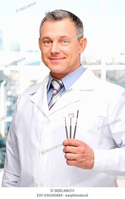 Photo of dentist holding stomatologist tools and looking at camera. Concept for teeth hygiene