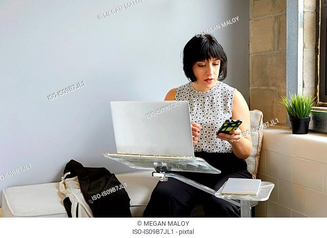 Woman sitting using laptop on laptop stand, holding smartphone