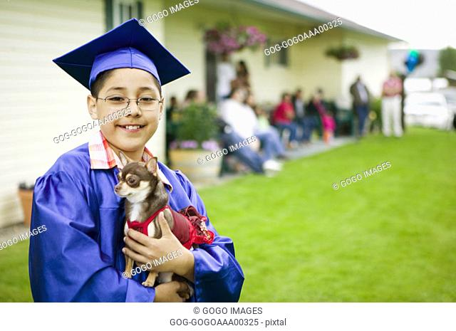 Boy 8-11 in graduation clothes, carrying puppy, close-up