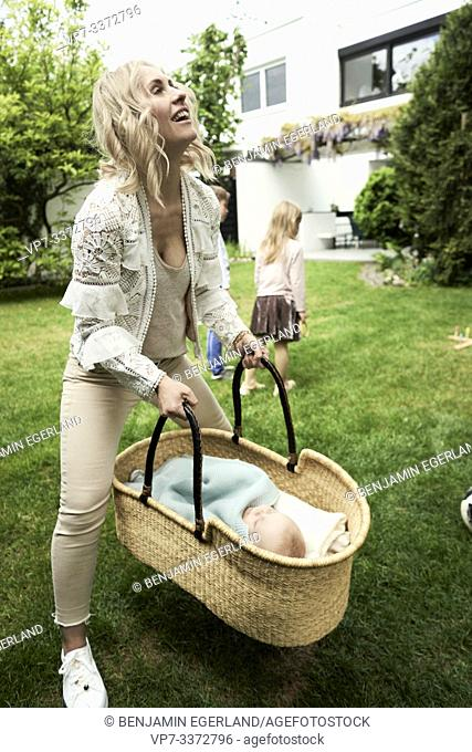 Woman holding carrycot with baby in garden
