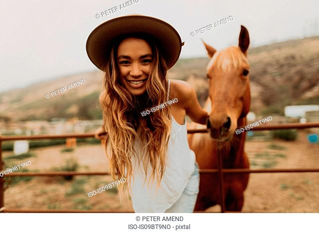 Young woman in felt hat in front of horse, portrait, Jalama, California, USA