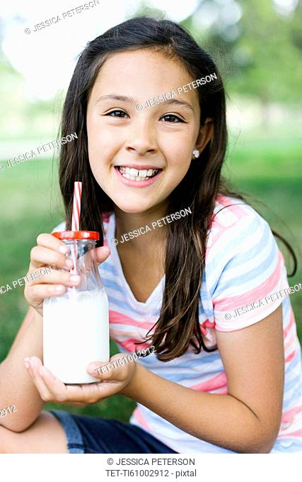 Girl (10-11) in park holding glass of milk with straw