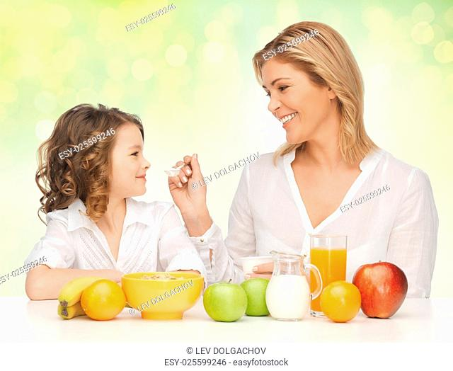 healthy eating, people, family and food concept - happy mother and daughter having breakfast over green holidays lights background