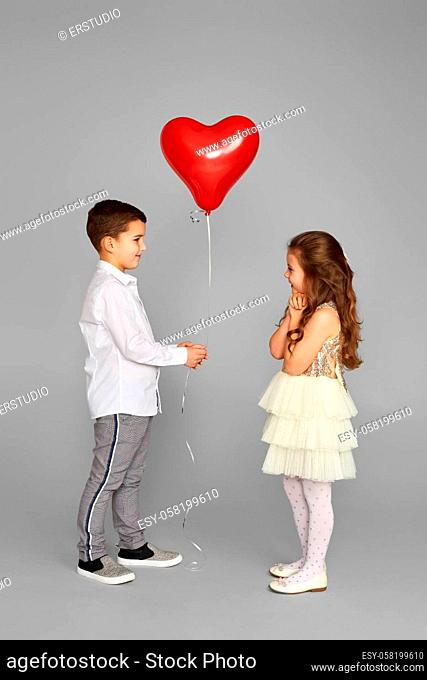 couple of little girl and boy with red heart balloons isolated on gray background. boy gives shy girl balloon. St. Valentine's Day