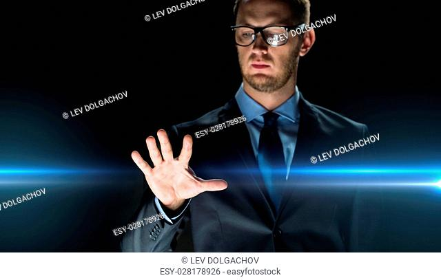 business, people, future technology and cyberspace concept - close up of businessman touching something imaginary over dark background and laser light