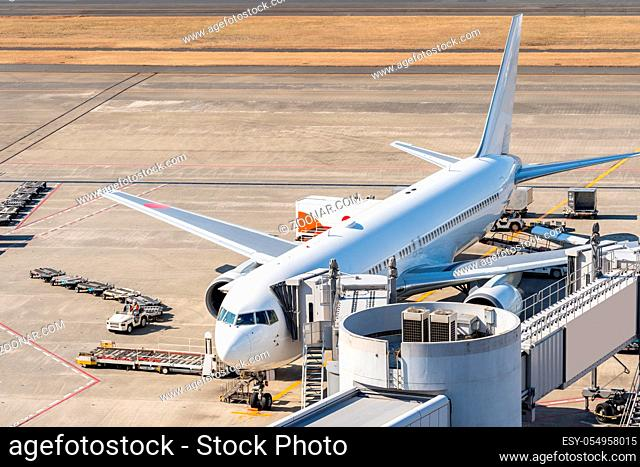 White Airplane unloading and loading passenger at Jet bridge in airport