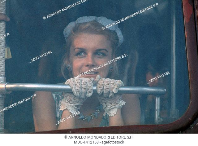 Ann Margret looks ahead behind a window. The actress Ann Margret, leaning on a bar behind a window wearing some lace gloves, looks ahead