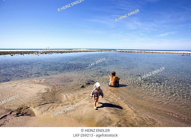 View at a woman and a child at a little lagoon in the sunlight, Punta Conejo, Baja California Sur, Mexico, America