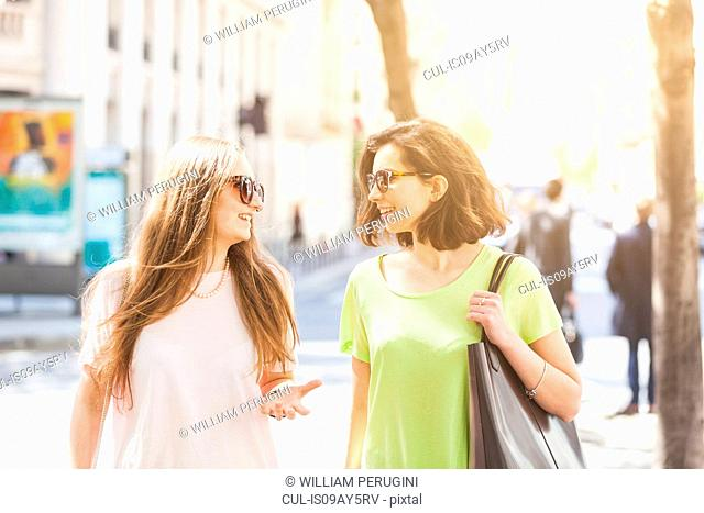 Two young women strolling on street chatting, Paris, France