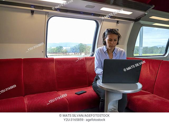 Business Woman Sitting on a Sofa and Working on Laptop in First Class in a Train in Switzerland