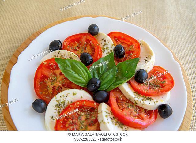 Mediterranean salad: sliced tomato, cottage cheese, black olives, basil and olive oil