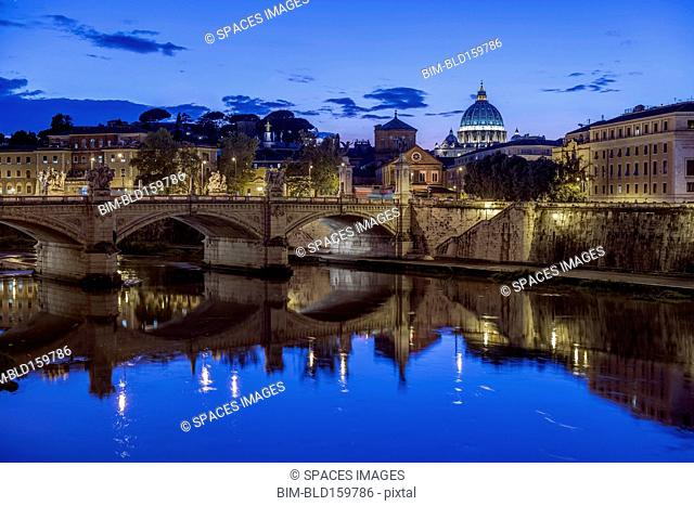 Ornate buildings and bridge illuminated at night, Rome, Italy