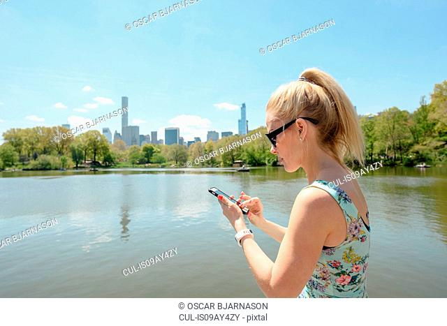 Female tourist smartphone texting by boating lake in Central Park, New York, USA