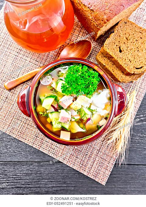 Cold soup okroshka from sausage, potatoes, eggs, radish, cucumber, greens and drink of kvass in a clay bowl, bread on napkin on wooden board background from...